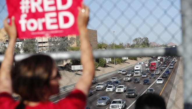 Teachers and educators, mostly from Garfield Elementary School, wave at afternoon rush hour traffic from the 10th St. pedestrian bridge over I-10 April 18, 2018.