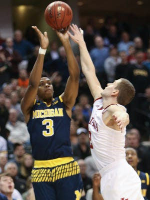 Michigan's Kameron Chatman hits the game-winning three-pointer over Indiana's Nick Zeosloft on Friday in Indianapolis.