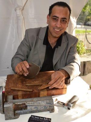 Tony Santana rolling up some cigars.