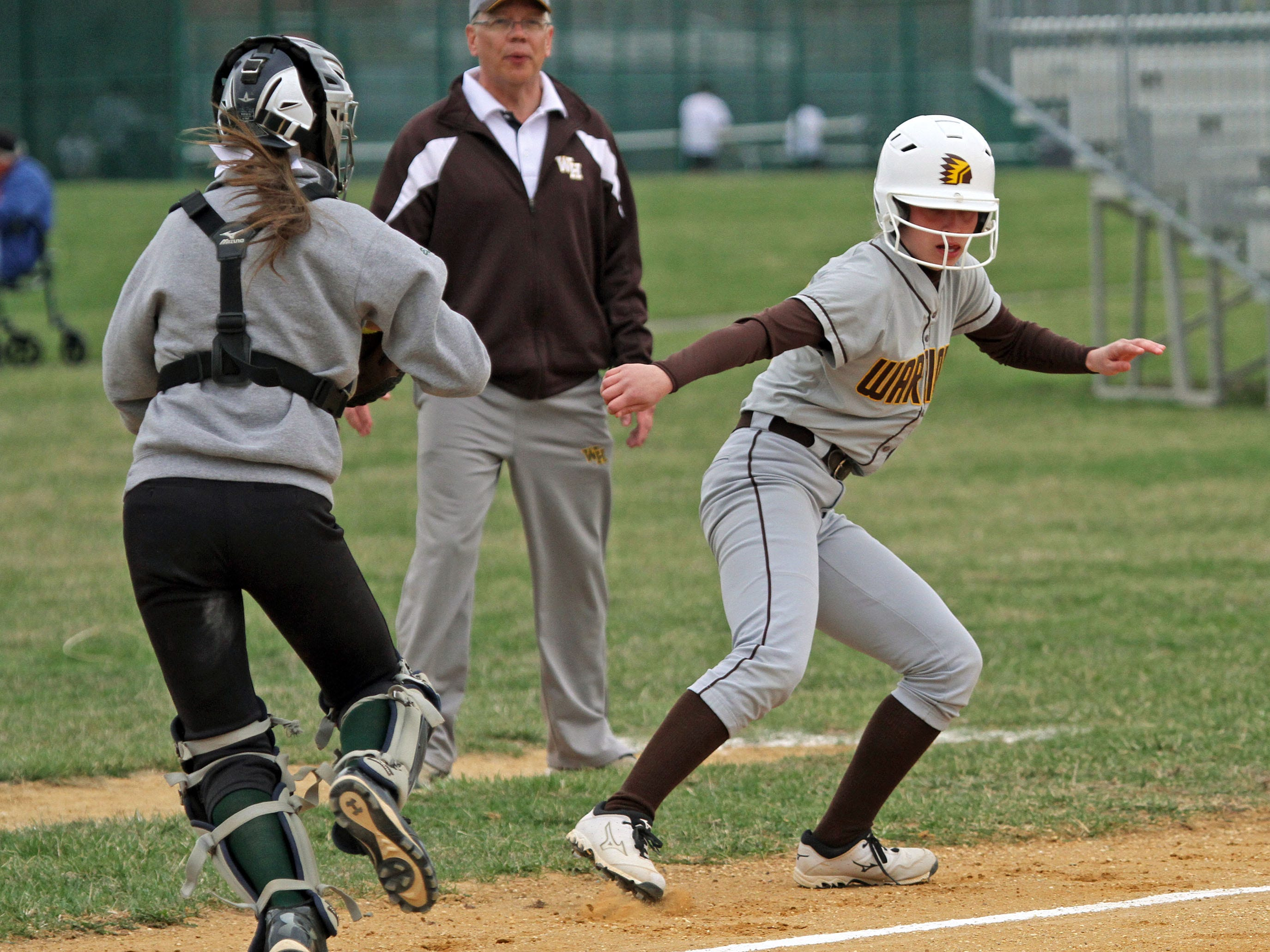 Watchung Hills' Alyssa Murray is caught in a run down between third and home. Montgomery catcher Kelsey Woodard chases her back to third where she was tagged out by Montgomery's Demitria Kitrine. This is action of Watchung Hills at Montgomery in girls softball.