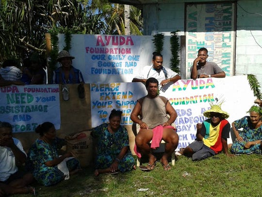 Some of the residents in one of the atolls in the Federated States of Micronesia show their gratitude after receiving relief goods, including blankets, and food following Typhoon Maysak last year.