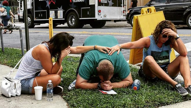 People grieve near Pulse nightclub in Orlando on Sunday. The club opened in 2004 after the owner's brother died of AIDS.