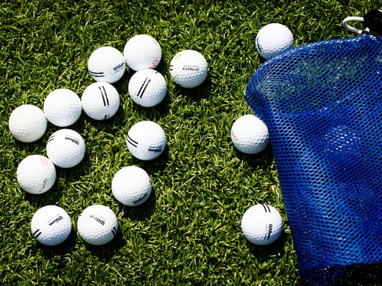 An assortment of golf balls is scattered on the driving range during a junior summer golf camp at Stoneybrook Golf Club in Estero, Fla. on Monday, July 25, 2016.