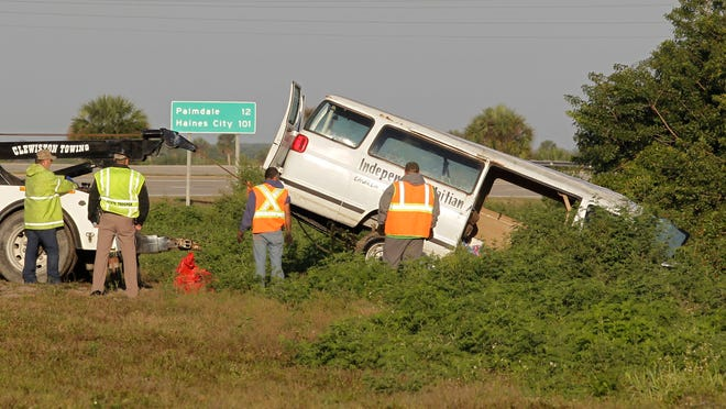 Workers pull a van out of a canal at the intersection of U.S. 27 and State Road 78 West on March 30 near Moore Haven. Eight people were killed and 10 injured when the church van ran through a stop sign, crossed all four lanes of a rural highway and crashed into in a canal.