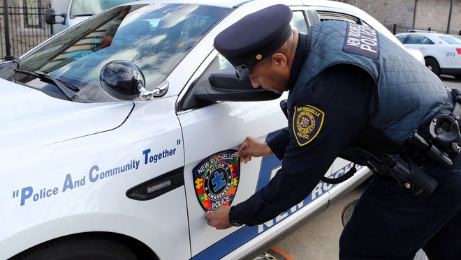 The New Rochelle police started an Autism Patch Challenge, led by Det. Chris Greco and his wife Tracy, who have an autistic son. Here, Det. Terrence Fudge, applies an autism awareness patch at New Rochelle police station.