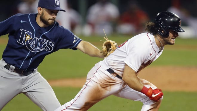 Boston Red Sox outfielder Andrew Benintendi (right), pictured during a game against the Tampa Bay Rays on Aug. 11, 2020, was added to Boston's 40-man roster on Saturday.