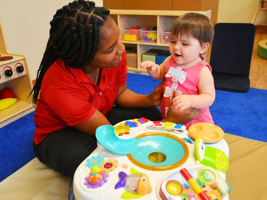 Teacher T'Keyia Woodberry works with Mia Salamone in the infant room at La Petite Academy in Rocklege.  The Children's Services Council in Brevard is seeking to add a tax referendum to the November ballot to raise money that could be used to benefit children who attend facilities like La Petite in Rockledge. The tax will go before the County Commissioners on July 24.