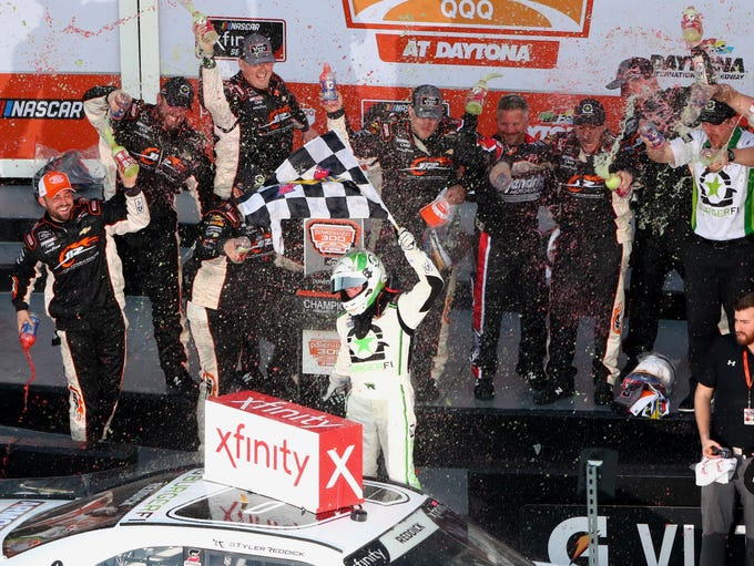 Tyler Reddick waves the checkered flag and celebrates