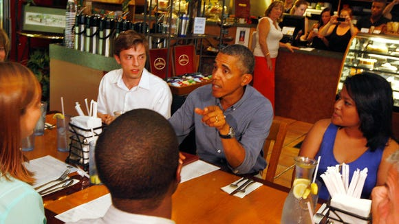 President Barack Obama talks to a table of patrons inside Magnolia's on Park Ave. in Rochester Thursday, Aug. 22, 2013 as he made an unexpected stop for lunch at the popular Rochester cafe.  Seated with the President are clockwise from the President, Wesline Manuelpillai, a sophomore at the University of Rochester, Brandon McDonald, University of Rochester grad, Evalyn Gleason, also a University of Rochester grad, and Doug Brady, a junior at the University of Rochester.