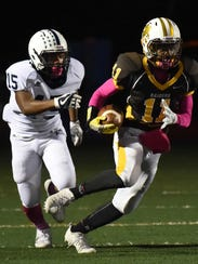North Farmington's sophomore running back Myles Greshman (11) works his way up field against the defensive efforts of Farmington junior Nate Shaw (15) on Oct. 13.
