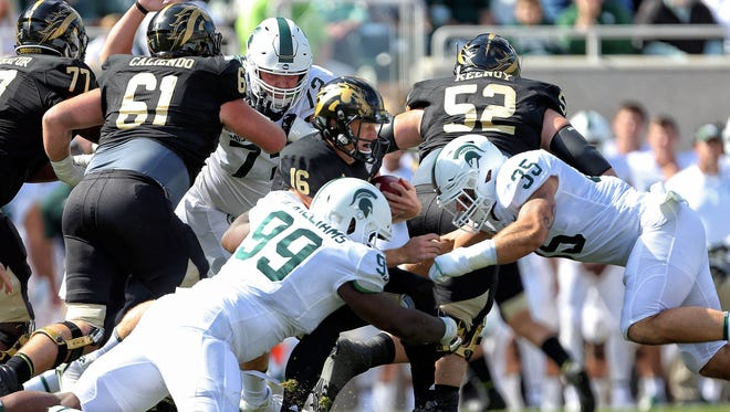 Sep 9, 2017; East Lansing, MI, USA; Western Michigan quarterback Jon Wassink is sacked by Michigan State defensive tackle Raequan Williams (99) and linebacker Joe Bachie (35) in the first quarter at Spartan Stadium.