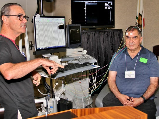 Neurology Tech Patrick Bartlett, (left) demonstrates how an electroencephalogram (EEG) is created. Assad Kastiro (right), is one of 37 middle- and high-school science teachers who visited Desert Regional Medical Center on July 24 as part of Project Prototype, a state-funded initiative to strengthen the region's ability to prepare students for careers in Science, Technology, Engineering, and Math (STEM).