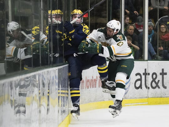 Catatmounts forward Rob Darrar (23) checks Michigan's Nicholas Boka (27) into the boards during the men's hockey game between the Michigan Wolverines and the Vermont Catamounts at Gutterson Field House on Friday night October 28, 2016 in Burlington. (BRIAN JENKINS/for the FREE PRESS)