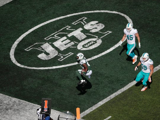 New York Jets running back Bilal Powell (29) passes Miami Dolphins' Chase Allen (59) and Mike Hull (45) for a touchdown during the second half of an NFL football game, Sunday, Sept. 24, 2017, in East Rutherford, N.J. (AP Photo/Seth Wenig)