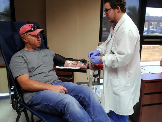 Blood bank trainer Tex Waller draws blood from Abilene