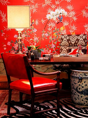 In this photo provided by Burnham Design, bold red wallpaper and upholstery are combined with neutral colors to create a lively but cohesive design for this home office, created by Betsy Burnham of Burnham Design.