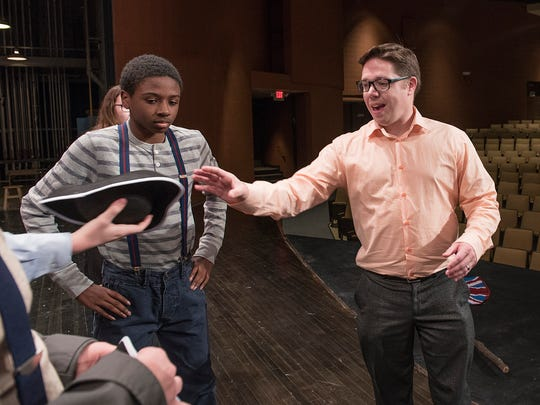 Director Greg Wiklanski takes a pirate hat from a cast member. At left, Peter Pan, played by Chandler Motley.