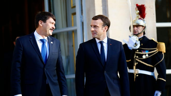 French President Emmanuel Macron, right, and Hungarian President Janos Ader leave after their talks at the Elysee Palace, in Paris, Tuesday, Dec. 12, 2017.