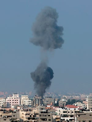 Smoke rises over Gaza City, in northern Gaza Strip, after an Israeli strike, minutes before 8 a.m. (0500 GMT), the time agreed for a preliminary 72-hour cease-fire, on Tuesday Aug, 5, 2014. Israel and Hamas on Monday accepted an Egyptian cease-fire proposal meant to halt a bruising month-long war that has claimed nearly 1,900 Palestinian lives, raising hopes that the bloodiest round of fighting between the bitter enemies could finally be coming to an end.