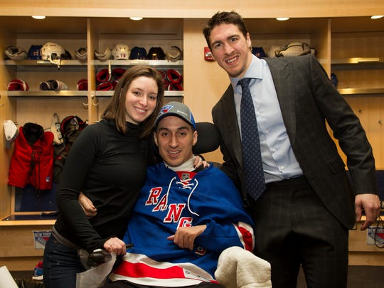 "Former Pelham hockey player Gino Mangiafridda, center, draws inspiration in his struggle to walk again from girlfriend Megan Seccante and Rangers defenseman Ryan McDonagh. Seccante says McDonagh ""doesn't do his one deed and then back off."""
