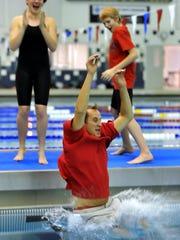 Canandaigua head coach Bob Black goes into the pool