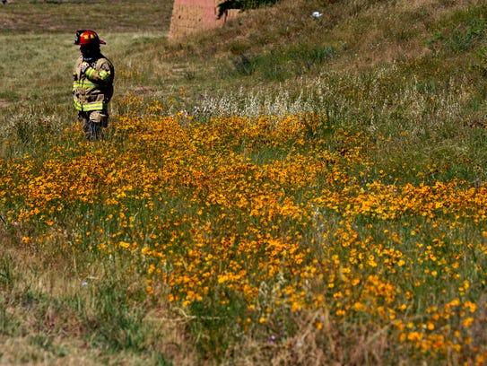 An Abilene firefighter surveys an overturned 18-wheeler on the State Highway 36 northbound on-ramp for Loop 322 Wednesday.