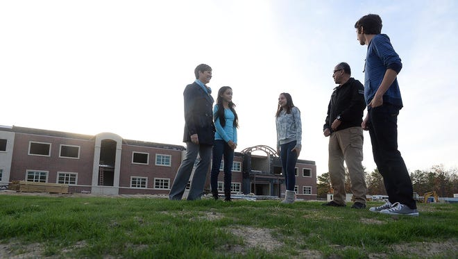 CCTEC assistant principal Patty Robbins (left) and law enforcement program instructor Andre Lopez (second from right) talk Tuesday with prospective freshmen for the 2016 school year Jessenia Rivera, 13, of Millville, Chloe Swift, 12, of Millville, and Nikolas Casalinuovo, 13, of Vineland (from left), outside the school's new building, which remains under construction.