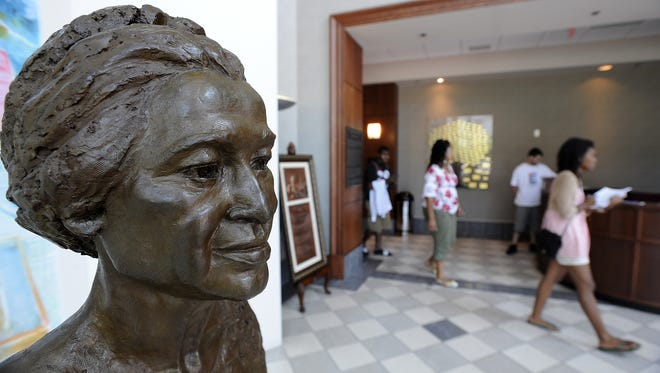 Students walk by a bust of Rosa Parks at the Rosa Parks Museum in Montgomery.