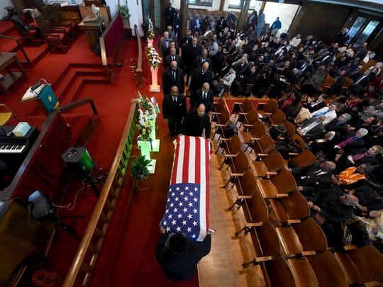 The draped covered casket of Voni Grimes is wheeled out of the church following his celebration of life ceremony at Small Memorial AME Zion Church on Saturday.