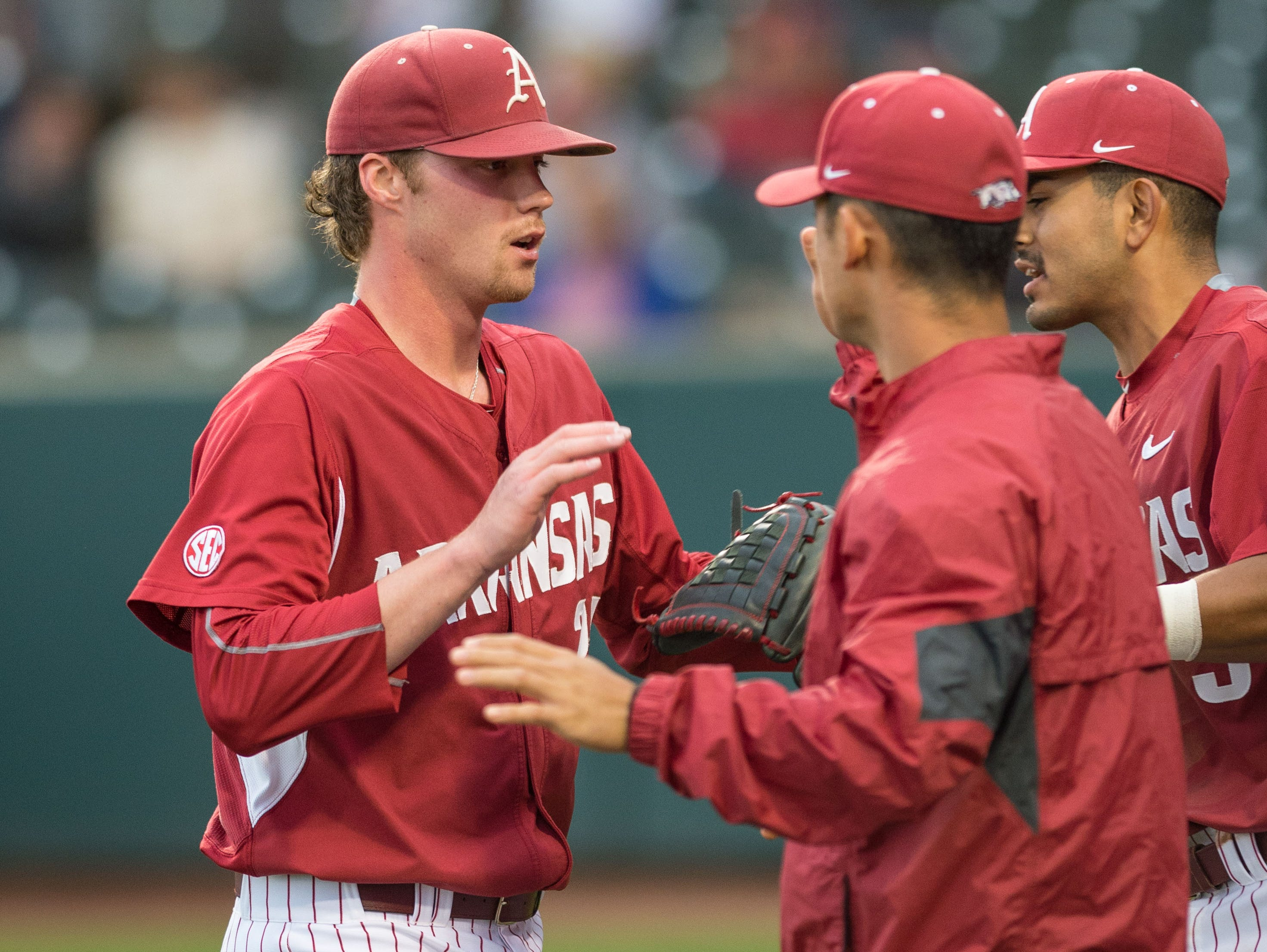 Arkansas' Trey Killian, left, is greeted by teammates after pitching against Mississippi State on Friday night at Baum Stadium in Fayetteville.