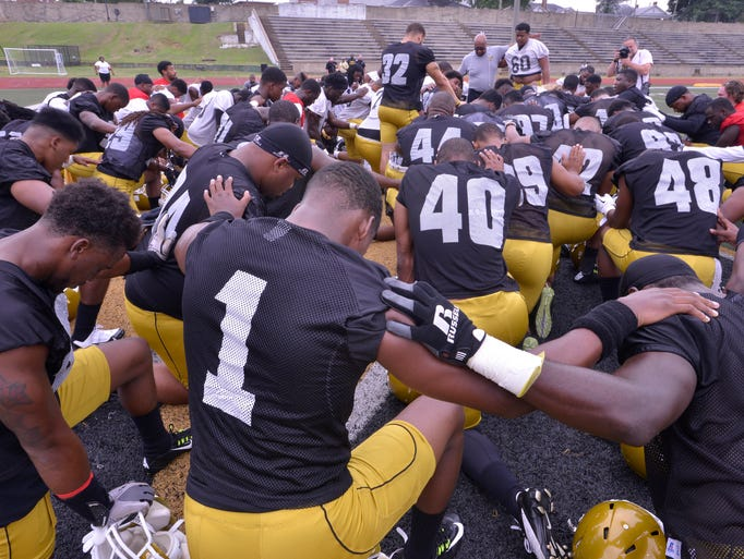 Alabama State University football players huddle and pray before the start of practice on Friday, Aug. 1, 2014.
