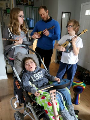 The entire family participates in the music therapy session with Elias Wendland, 7, of Liberty Township - his siblings Livia, 12, and Leo, 10, along with their dad Stephen.