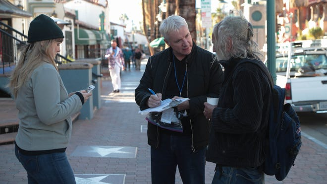 James Williamson, center, talks to a homeless man in downtown Palm Springs during the annual point-in-time count, Tuesday, January 23, 2018.