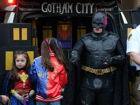 Batman hands out candy to trick-or-treaters during the Tom Green County Sheriff's Office's second annual Halloween Trunk or Treat Tuesday, Oct. 31, 2017.