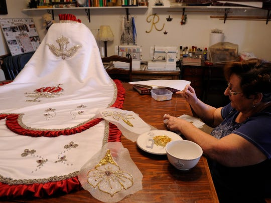 """Rosie Dias, 72, of Tulare continues to sew capes and embellish gowns for Portuguese festas throughout the Central Valley and California. Here, she sews beads onto an applique of a lily. The cape at left she made for Brianne Azevedo, the current junior queen for Tulare. It was in for repairs. """"This one was already on the road,"""" Dias said."""