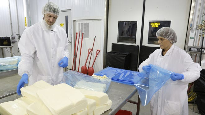 Eric Teska of Silver Creek, left, and Denise Poole of Adell, inspect and prepare loaves of mozzarella cheese for vacuum packing at Fairplay in Plymouth. Fairplay is a division of Titletown Cheese Trading Company.