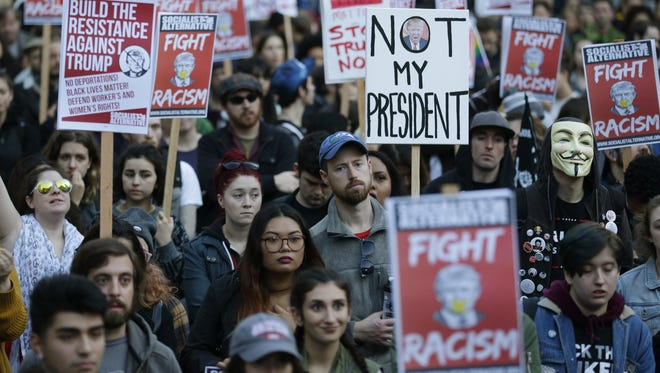 People hold signs at a protest against the election of President-elect Donald Trump in downtown Seattle.