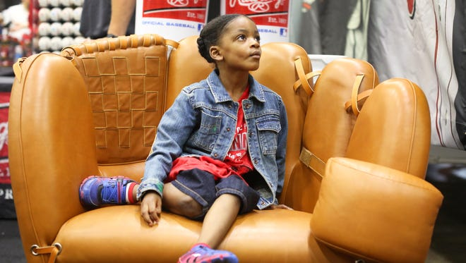 Alexander Wooten, 3, of Avondale, gets his photo taken while sitting in the Rawlings leather chair during FanFest, at the Convention Center. It's all part of the All-Star Week festivities.
