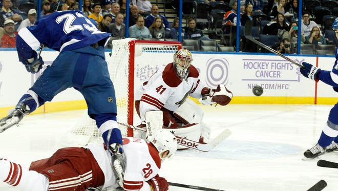 Arizona Coyotes goalie Mike Smith (41) looks at the puck as Tampa Bay Lightning right wing J.T. Brown (23) jumps over Arizona Coyotes defenseman Michael Stone (26)  during the second period at Amalie Arena on Oct. 28, 2014.