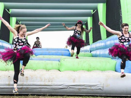 Women donning tutus run through the Insane Inflatable
