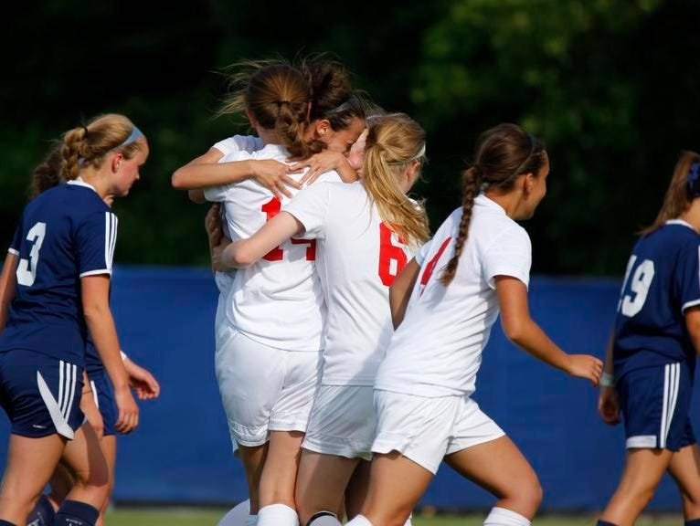 St. Johns' Lexi McPherson, center, Chloe Durgan, left, Chelsie Smith (6) and Abbey Schuelke, rear, celebrate McPherson's goal against East Lansing.