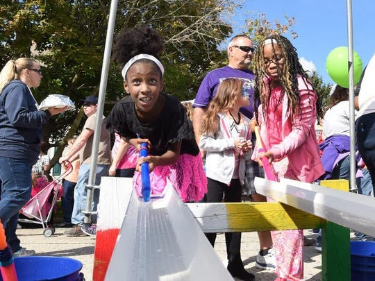 Bre'azia Upshur, of Bridgeville (left) and her sister Isis competing against each other in the duck race game at one of the street vendors at the Apple Scrapple Festival in 2015.