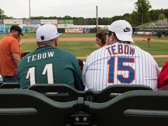 Two fans wearing Tim Tebow jerseys await the start of the game.