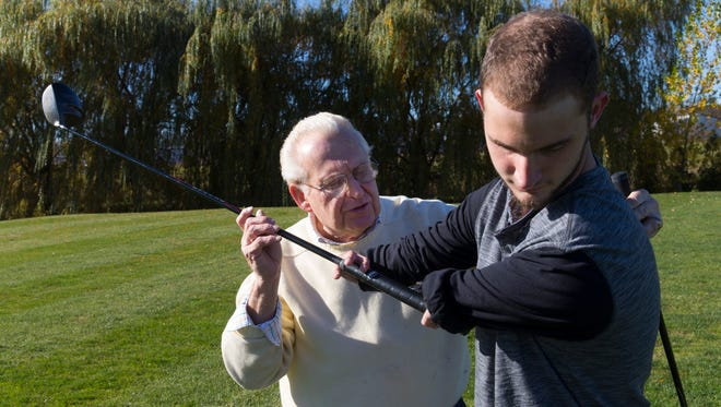 Ricky Kaufert, born with deformed arms that end at the elbows, gets help with his golf swing from Bob Burns.