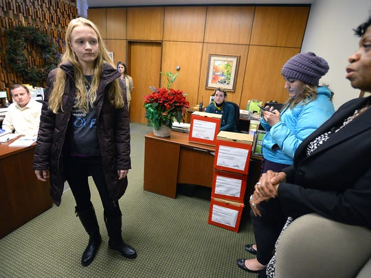 MSU student Emily Kollaritsch, standing left, speaks to MSU Vice President for Student Affairs and Services Denise Maybank, right, during a sit in at the president's office on campus in East Lansing on Dec. 10, 2014. Kollaritsch, then a senior, spoke to the group and said she was sexually abused while a freshman at MSU and reported it to the university. Kollaritsch and three other women have sued MSU in federal court over its handling of their sexual assault allegations.