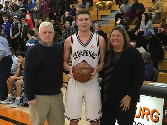 Cedarburg senior John Diener poses with his parents, Tom and Christina, after scoring his 2,000th point in a 57-52 victory over Nicolet during the 2017-18 season.