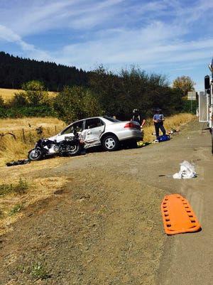 Oregon State Police troopers examine the scene of a two-vehicle crash that left four people injured Sunday morning.
