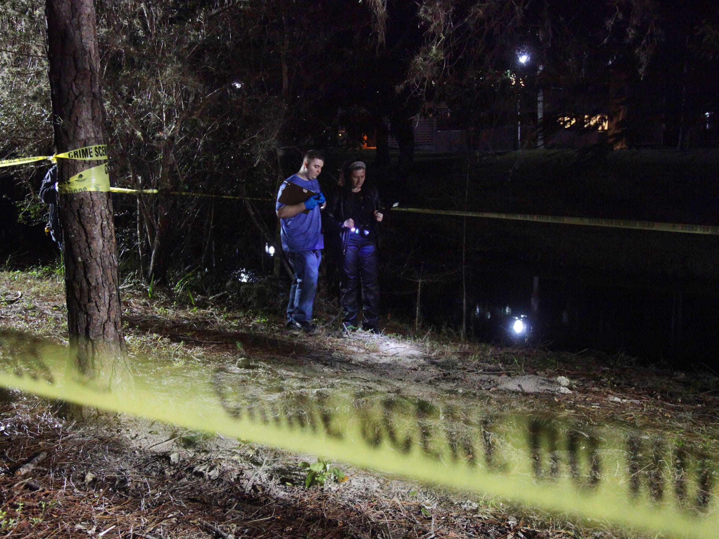 FSW students, Brandon Cramer, and Kim Bliss investigate the scene after using crime scene tape to isolate the suspicious area during Dennis Fahey's Crime Scene class.