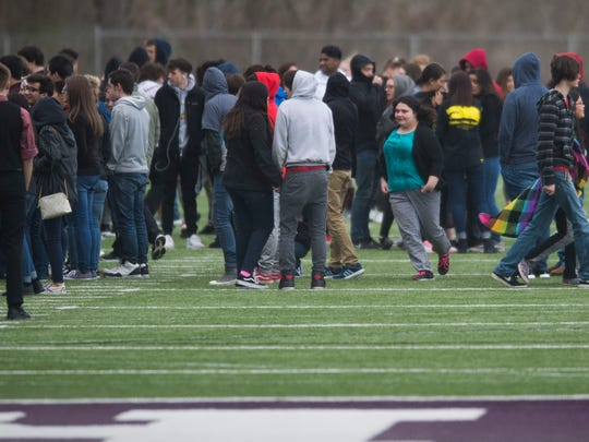 Students at Sevier County High School walk out onto the football field at 10 a.m. in tribute to the 17 victims of the Marjory Stoneman Douglas High School shooting in Parkland, Florida, in Sevierville Wednesday, March 14, 2018.