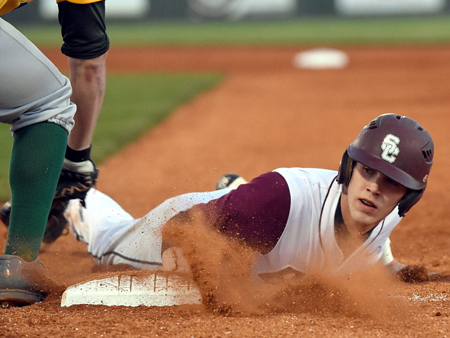 Station Camp High junior Thomas Zazzaro slides safely back into first base as Gallatin senior first baseman Carlos Hernandez receives a first-inning pickoff throw.